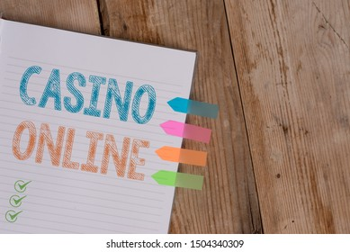 Handwriting text writing Casino Online. Concept meaning Computer Poker Game Gamble Royal Bet Lotto High Stakes Striped note book four colored arrow banners reminder wooden background.