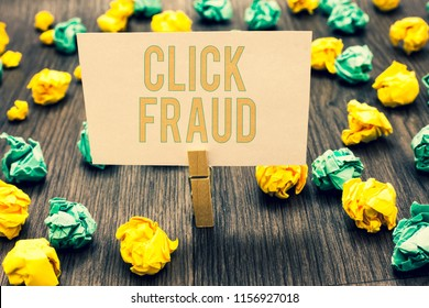 Handwriting text writing Click Fraud. Concept meaning practice of repeatedly clicking on advertisement hosted website Clothespin holding light pink note paper crumpled papers several tries.
