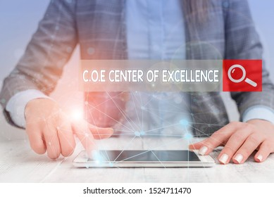 Handwriting text writing Coe Center Of Excellence. Concept meaning being alpha leader in your position Achieve Female human wear formal work suit presenting presentation use smart device.