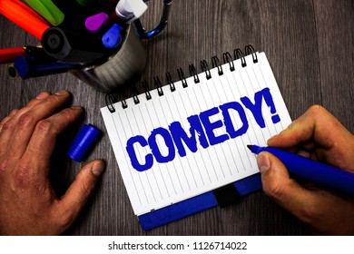 Handwriting text writing Comedy Call. Concept meaning Fun Humor Satire Sitcom Hilarity Joking Entertainment Laughing Man hold holding marker notebook ideas markers wooden table inspiration.