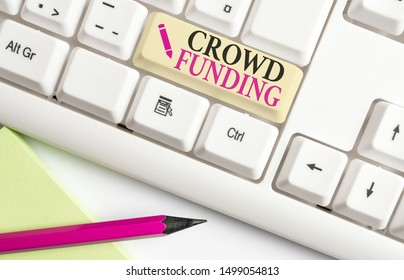 Handwriting text writing Crowd Funding. Concept meaning Fundraising Kickstarter Startup Pledge Platform Donations White pc keyboard with empty note paper above white background key copy space.
