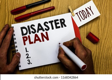 Handwriting text writing Disaster Plan. Concept meaning Respond to Emergency Preparedness Survival and First Aid Kit Man holding marker notebook clothespin reminder wooden table cup coffee.