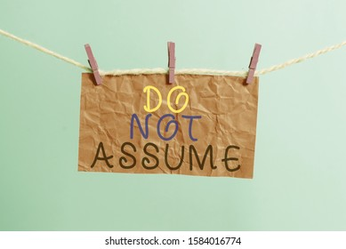 Handwriting text writing Do Not Assume. Concept meaning Ask first to avoid misunderstandings confusion problems Clothesline clothespin rectangle shaped paper reminder white wood desk.