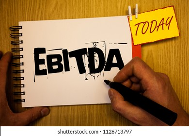 Handwriting text writing Ebitda. Concept meaning Earnings Before Interest Taxes Depreciation Amortization Abbreviation Man hold holding black marker notebook clothespin today wooden table.