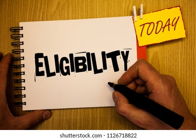 Handwriting text writing Eligibility. Concept meaning State of having the right for doing or obtain something Proper Man hold holding black marker notebook clothespin today wooden table.