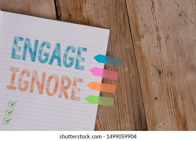 Handwriting text writing Engage Ignore. Concept meaning Silent Treatment Manipulative Punishment Sulking Shunning Striped note book four colored arrow banners reminder wooden background.