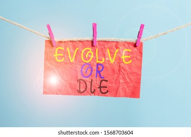 Handwriting text writing Evolve Or Die. Concept meaning Necessity of change grow adapt to continue living Survival Clothesline clothespin rectangle shaped paper reminder white wood desk.