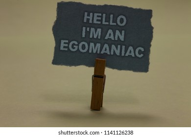 Handwriting text writing Hello I am An Egomaniac. Concept meaning Selfish Egocentric Narcissist Self-centered Ego Paperclip retain ash color written torn thick page on shadow ash floor.