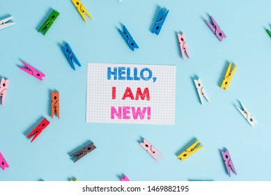 Handwriting text writing Hello I Am New. Concept meaning used as greeting or to begin telephone conversation Colored clothespin rectangle shaped reminder paper light blue background.