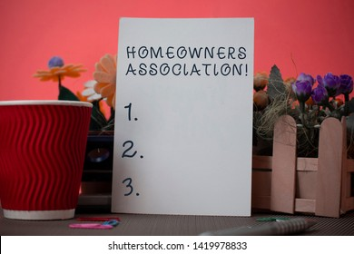 Handwriting text writing Homeowners Association. Concept meaning Organization with fee for upkeeps of Gated Community Flowers and stationary plus plain sheet with paper big cup above a table.