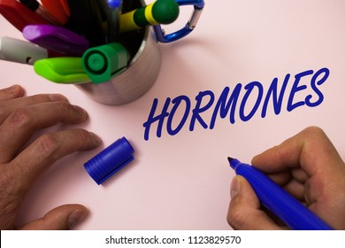 Handwriting text writing Hormones. Concept meaning Regulatory substance produced in an organism to stimulate cells Man working inspiration holding marker notebook ideas white background.