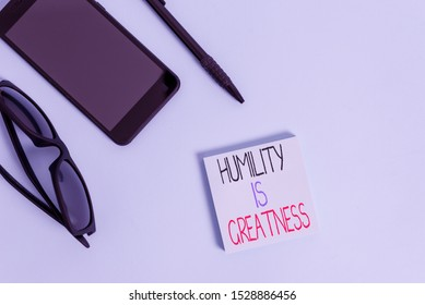 Handwriting text writing Humility Is Greatness. Concept meaning being Humble is a Virtue not to Feel overly Superior Eyeglasses colored sticky note smartphone cell pen cool pastel background.
