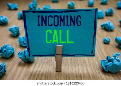 Handwriting text writing Incoming Call. Concept meaning Inbound Received Caller ID Telephone Voicemail Vidcall Clothespin holding blue paper note crumpled papers several tries mistakes.