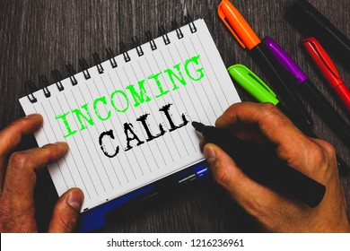 Handwriting text writing Incoming Call. Concept meaning Inbound Received Caller ID Telephone Voicemail Vidcall Man holding marker notebook paper communicating ideas Wooden background.