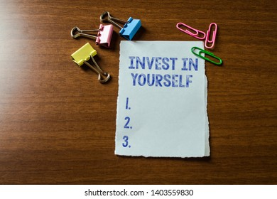Handwriting text writing Invest In Yourself. Concept meaning learn new things or materials thus making your lot better Blank stationary paper set three colored clips binders lying wooden table.