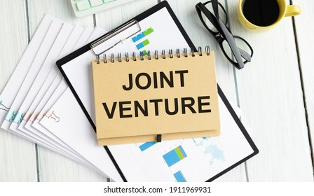 Handwriting text writing Joint Venture. Concept meaning Collaboration Arrangement Parties Partnership Team marker notebook paper communicating ideas Wooden background.