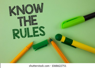 Handwriting text writing Know The Rules. Concept meaning Understand terms and conditions get legal advice from lawyers written Plain Green background Pens next to it.