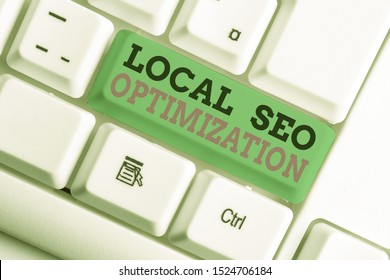 Handwriting text writing Local Seo Optimization. Concept meaning increase Search Visibility to Rank on Top list White pc keyboard with empty note paper above white background key copy space.