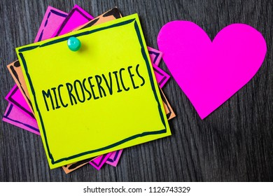 Handwriting text writing Microservices. Concept meaning Software development technique Decomposing an application Border sticky remember cards love heart pinned dark woody background.
