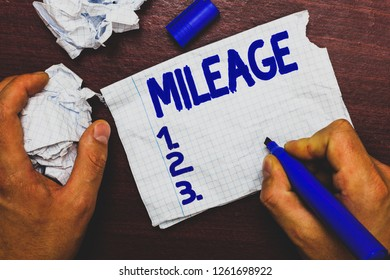 Handwriting text writing Mileage. Concept meaning Number of miles travelled or covered Display panel Car instrument Man holding marker notebook page crumpled papers several tries mistakes.