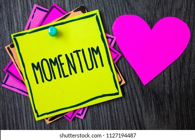 Handwriting text writing Momentum. Concept meaning Quantity motion in moving body Product of mass and velocity Border sticky remember cards love heart pinned dark woody background.