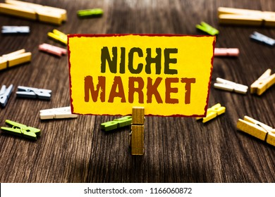 Handwriting text writing Niche Market. Concept meaning Subset of the market on which specific product is focused Clothespin holding yellow paper note several clothespins wooden floor.