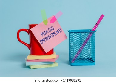 Handwriting text writing Process Improvement. Concept meaning Optimization Meet New Quotas Standard of Quality Cup note arrow banners stacked pads metal pen holder pastel background.