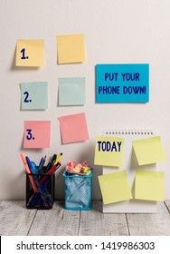 Handwriting text writing Put Your Phone Down. Concept meaning end telephone connection saying goodbye caller 10 Sticky Notes Card on Wall Spiral Notebook 2 Pencil Pots on Work Desk.