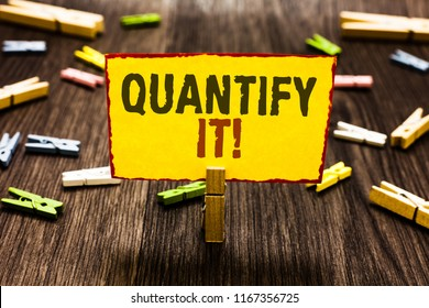 Handwriting text writing Quantify It. Concept meaning Measure the size or amount of something and express in numbers Clothespin holding yellow paper note several clothespins wooden floor.