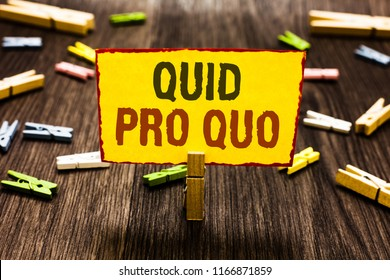 Handwriting text writing Quid Pro Quo. Concept meaning A favor or advantage granted or expected in return of something Clothespin holding yellow paper note several clothespins wooden floor.