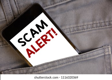 Handwriting text writing Scam Alert Motivational Call. Concept meaning Safety warning to avoid fraud or virus attacksConcept on cell phone into jean pocket white screen black and red letters.