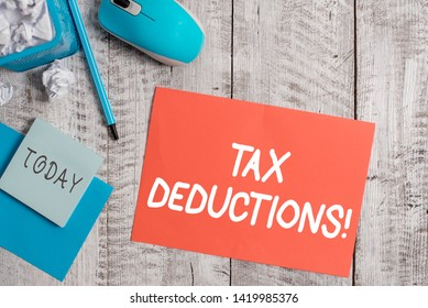 Handwriting text writing Tax Deductions. Concept meaning reduction income that is able to be taxed of expenses Crumpled paper in bin and computer mouse with stationary on wooden backdrop.