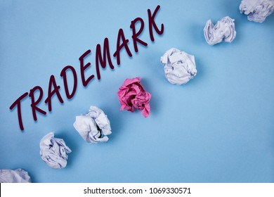 Handwriting text writing Trademark. Concept meaning Legally registered Copyright Intellectual Property Protection written on Plain Blue background Crumpled Paper Balls next to it.