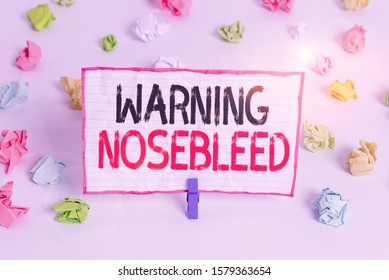 Handwriting text writing Warning Nosebleed. Concept meaning caution on bleeding from the blood vessels in the nose Colored crumpled papers empty reminder white floor background clothespin.