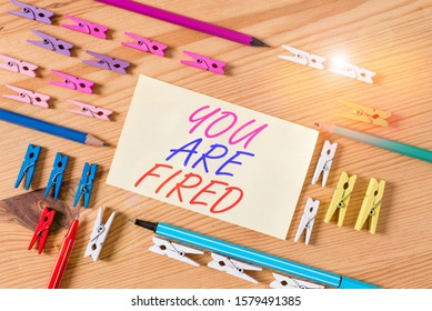 Handwriting text You Are Fired. Concept meaning Getting out from the job and become jobless not end the career Colored clothespin papers empty reminder wooden floor background office.