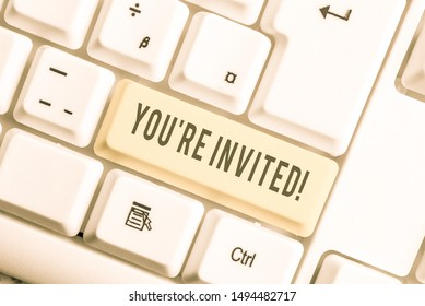 Handwriting text You Re Invited. Concept meaning make a polite friendly request to someone go somewhere White pc keyboard with empty note paper above white background key copy space.
