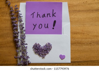 Handwriting Thank you Card and envelope with purple salvia officinalis flowers on rustic wooden background. Conceptual image to say thank you to someone.