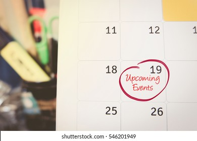 handwriting word up coming events on calendar over blurred background.selective focus shot