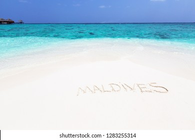 "Handwriting word ""Maldives"" on maldivian beach drawn on sand, travel destinations concept card"