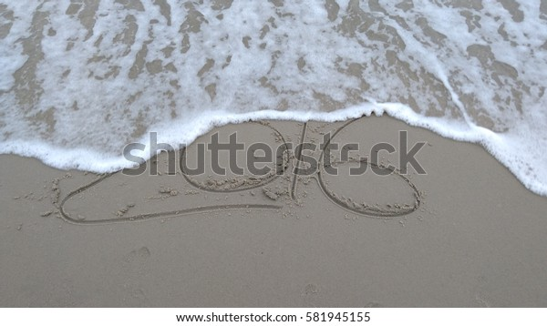 "Handwriting words ""2016"" on sand of beach"