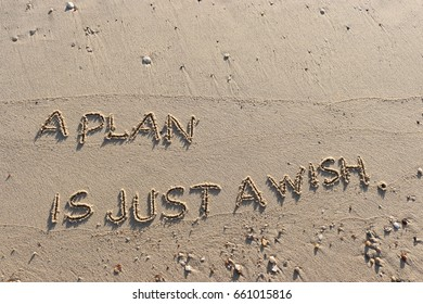 """Handwriting  words """"A PLAN IS JUST A WISH."""" on sand of beach."""