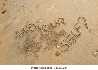 """Handwriting  words """"AND YOUR SELF?"""" on sand of beach."""
