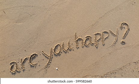 """Handwriting words """"are you happy?"""" on sand of beach"""