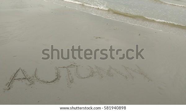 "Handwriting words ""AUTUMN"" on sand of beach"