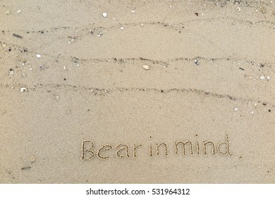 "Handwriting words ""Bear in mind"" on sand of beach"