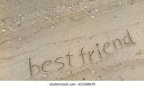 "Handwriting words ""best friend"" on sand of beach"