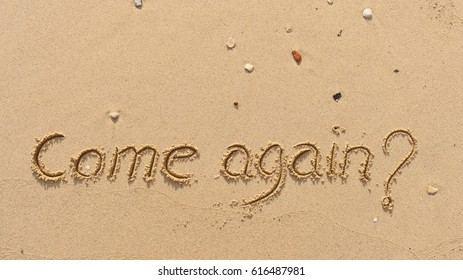 """Handwriting  words """"Come again?"""" on sand of beach."""