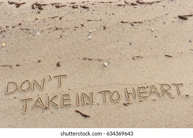 """Handwriting  words """"DON'T TAKE IN TO HEART."""" on sand of beach."""