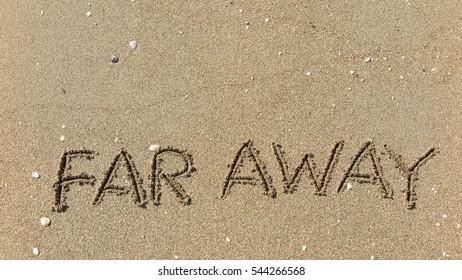 "Handwriting words ""FAR AWAY"" on sand of beach"