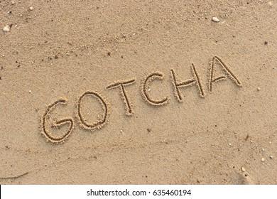 "Handwriting  words ""GOTCHA"" on sand of beach."
